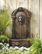 Garden fountain mounted on fence.